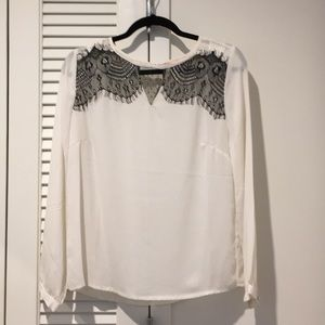 White shirt with black lace detail.